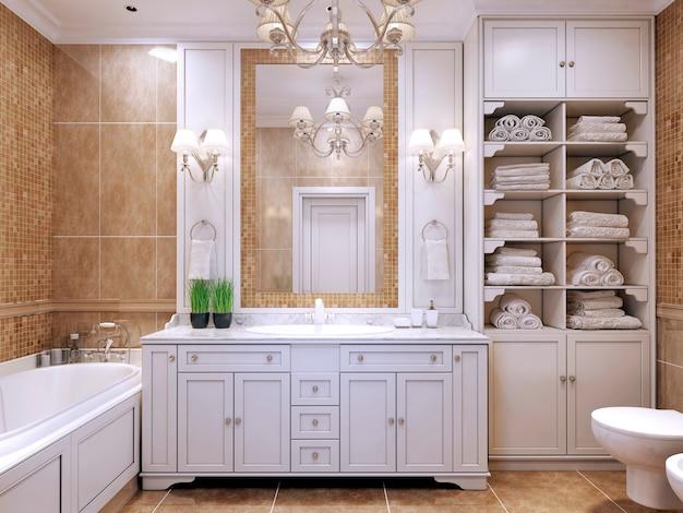 Móveis em banheiro clássico com banheiro de cor creme com móveis brancos e grande espelho com arandelas e lustre luxuoso.