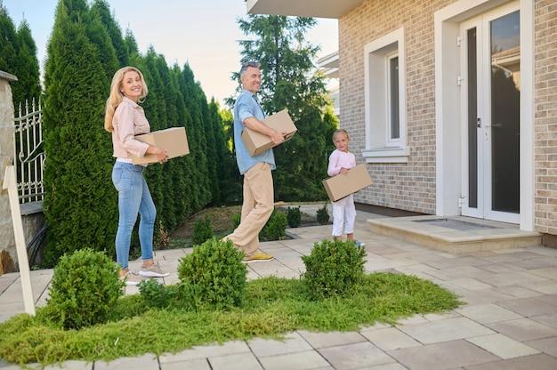 Movendo-se. sorrindo alegre, mãe, pai e filha caminhando com caixas de papelão para a casa em um dia bom