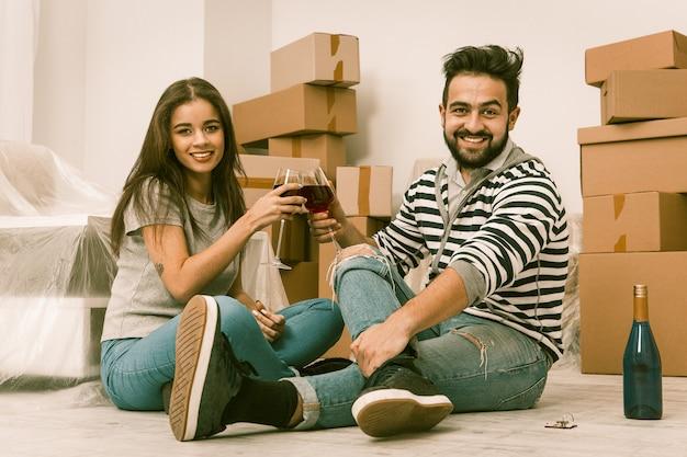 Movendo-se, tempo de alegria, jovem casal comemorando a realocação.