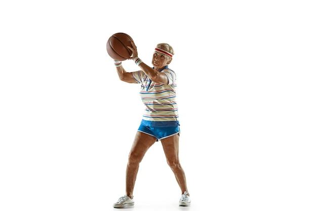 Mover. mulher sênior, vestindo roupas esportivas jogando basquete em fundo branco. modelo feminino caucasiano em ótima forma permanece ativo. conceito de esporte, atividade, movimento, bem-estar, confiança. copyspace.
