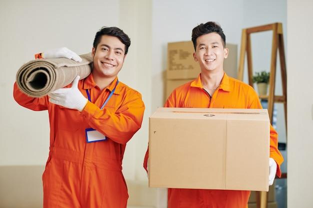 Movers carregando carpete e caixa de papelão