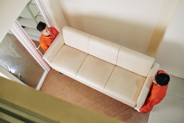 Movers carregando sofá de couro