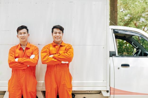 Movimentadores sorridentes em uniforme laranja