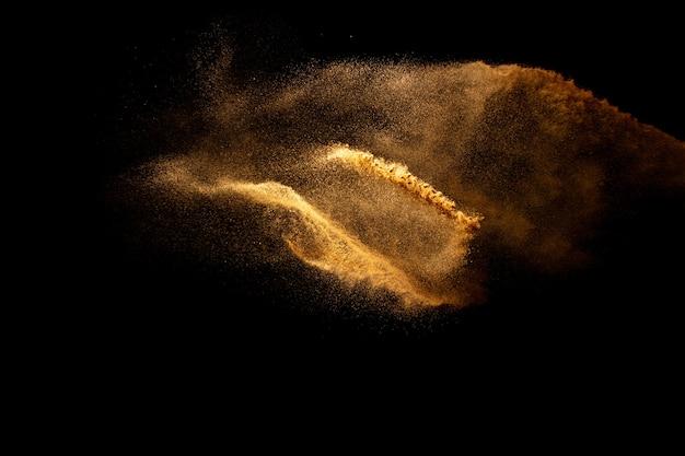Movimento abstrato borrado respingos de areia de cor marrom contra fundo preto.