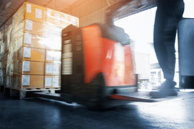 Movimento acelerado do trabalhador dirigindo a empilhadeira elétrica para descarregar as caixas de pacotes no armazém