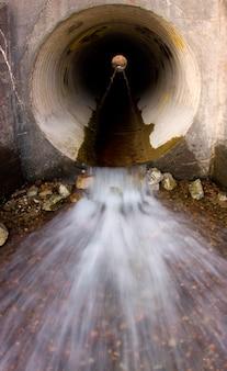 Movimento borrado de água espirrando para fora do tubo de esgoto de cimento