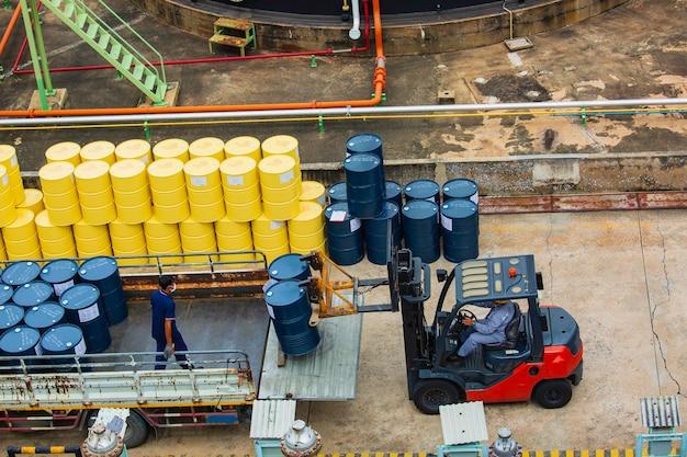 Movimento de empilhadeira de barris de óleo de vista superior para o trabalhador masculino de caminhão de transporte ajudar a organizar.