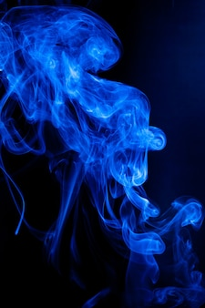 Movimento de fumaça azul sobre fundo preto.