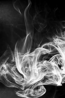 Movimento de fumaça branca sobre fundo preto.