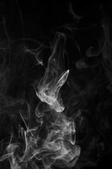 Movimento de fumaça sobre fundo preto, com espaço de cópia para escrever o texto