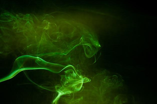 Movimento de fumaça verde sobre fundo preto.