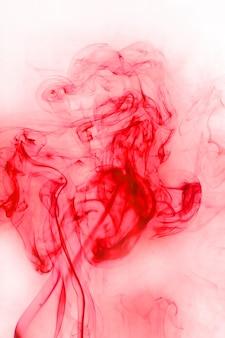Movimento de fumaça vermelha sobre fundo branco.