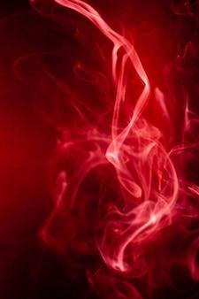 Movimento de fumaça vermelha sobre fundo preto.