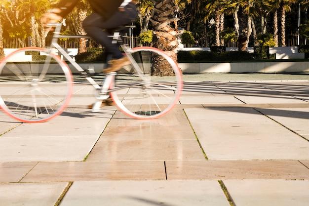 Movimento desfocado de uma pessoa a andar de bicicleta no parque