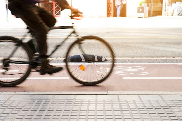 Movimento desfocado do ciclista andando na ciclovia perto da calçada