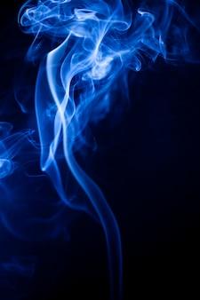 Movimento fumaça azul sobre fundo preto.