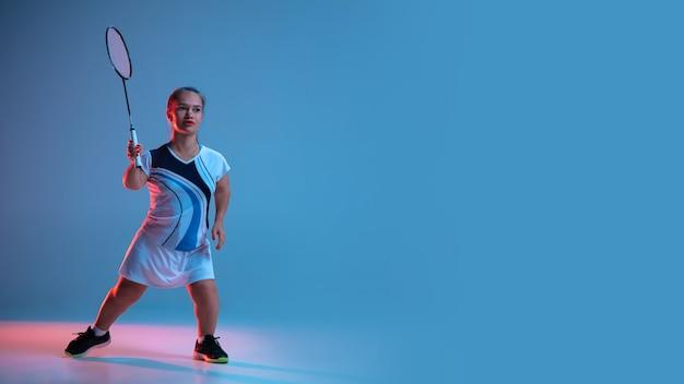 Movimento. linda mulher anã praticando badminton isolada em azul em luz de néon