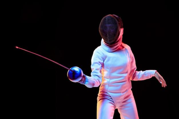 Movimento. menina adolescente em traje de esgrima com espada na mão, isolada na parede preta, luz de néon. jovem modelo praticando e treinando em movimento, ação. copyspace. esporte, juventude, estilo de vida saudável.
