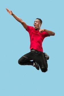 Movimento para a frente o jovem africano surpreso feliz pulando contra o fundo azul do estúdio