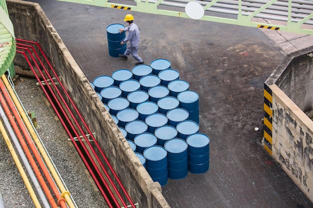 Movimento vertical de barris de óleo de vista superior para o trabalhador masculino ajudar a organizar.
