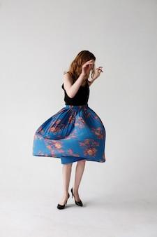 Movimentos borrados de jovem magrela caucasiana de saia azul, retrato de interiores