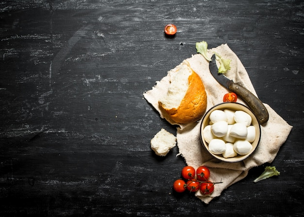 Mozzarella com pão fresco, tomate e verduras em um fundo preto de madeira