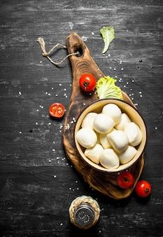Mozzarella em uma tigela com os tomates e ervas em um fundo preto de madeira
