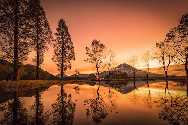 Mt. fuji com grandes árvores e lago ao nascer do sol em fujinomiya, japão.