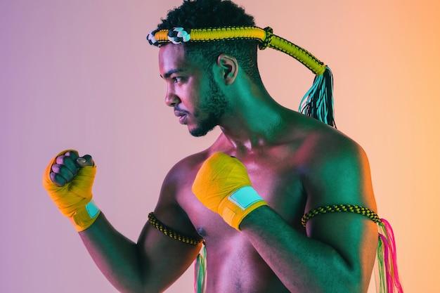 Muay thai. jovem exercitando o boxe tailandês em fundo gradiente em luz de néon.