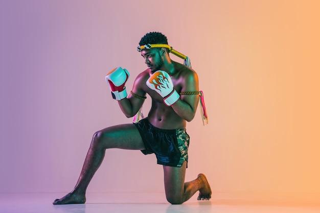 Muay thai. jovem exercitando o boxe tailandês na parede gradiente em luz de néon. lutador praticando, treinando artes marciais em ação, movimento. estilo de vida saudável, esporte, conceito de cultura asiática.