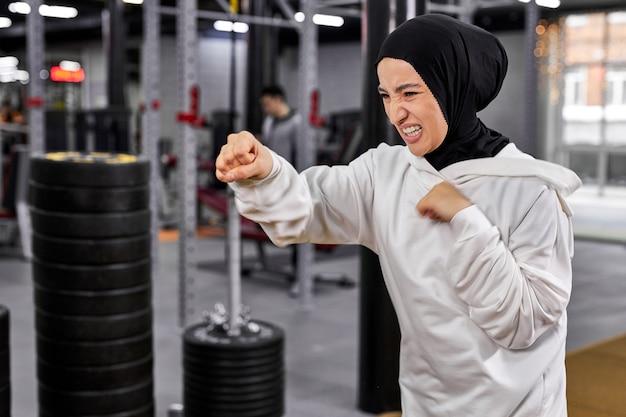 Muçulmana boxeadora em hijab white sportswear em pé em pose de lutador envolvida em boxe, mulher árabe fazendo exercícios, levando estilo de vida saudável. esporte em países islâmicos, conceitos de direitos das mulheres