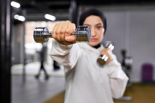 Muçulmano feminino treinando na academia usando halteres, tendo intenso treino sozinho no moderno centro de fitness, vestindo branco hijab esportivo. foco em halteres