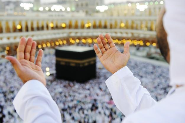 Muçulmano orando em mekkah com as mãos para cima