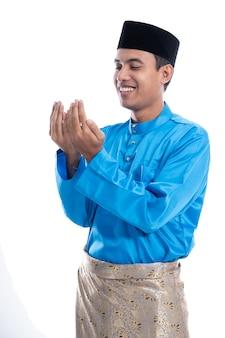 Muçulmanos masculinos com tampa de cabeça rezando