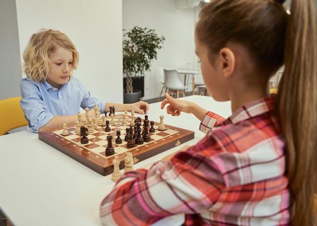 Mudança a cada movimento, um garotinho caucasiano concentrado, planejando seu movimento enquanto joga xadrez com