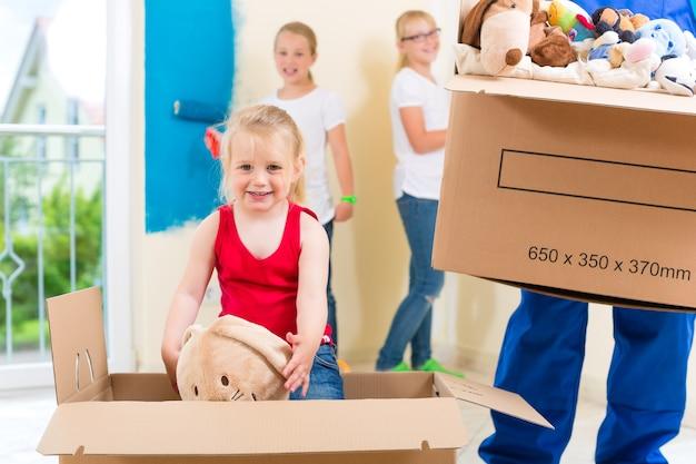 Mudança de casa da família com caixas cheias de coisas, eles estão pintando as paredes de sua nova casa