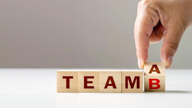 Mudança de cubos de madeira de team a para team b com as mãos de investidores