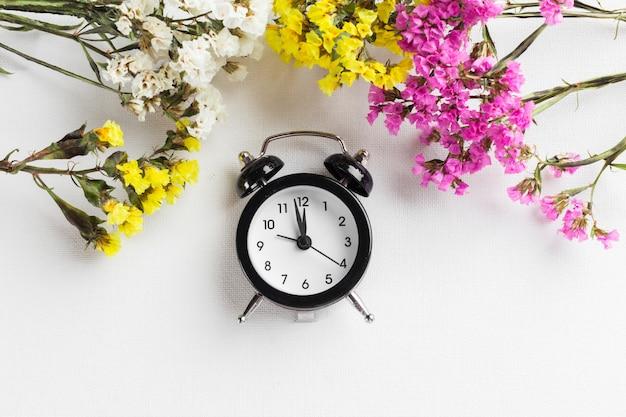 Mudança de horário de primavera com despertador e galhos de flores