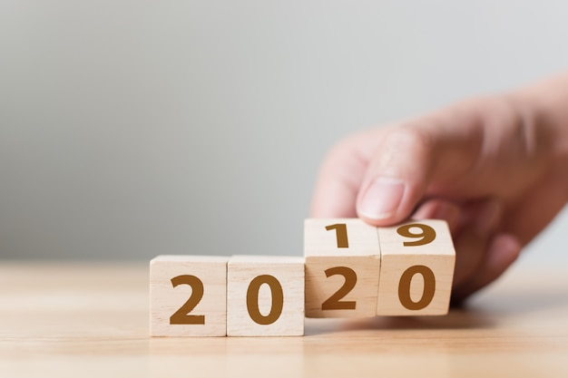 Mudança do ano novo 2019 para o conceito 2020. mão virar bloco de madeira do cubo