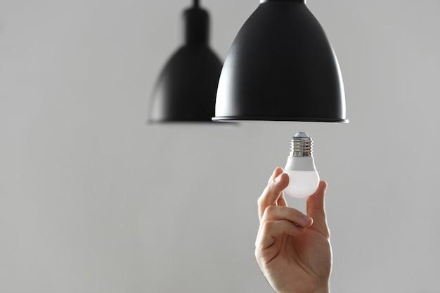 Mudando o bulbo para o bulbo conduzido na lâmpada de assoalho na cor preta. em fundo cinza claro