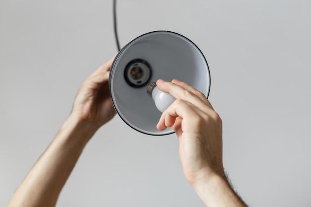 Mudando o bulbo para o bulbo conduzido na lâmpada de assoalho na cor preta.