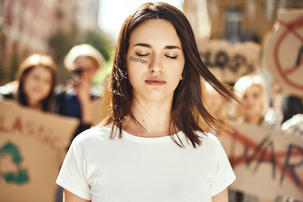 Mudando o mundo, jovem e corajosa mulher com a palavra liberdade escrita em seu rosto e