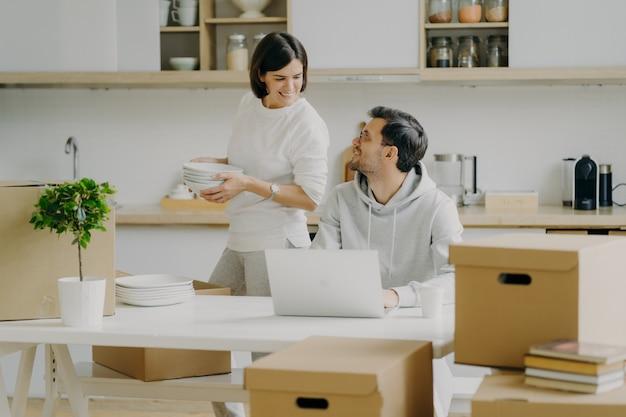Mudando para casa nova. casal feliz família descompactar pacotes de papelão com pratos