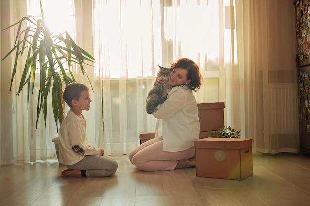Mudar para uma nova casa. feliz mãe e filho organizando caixas
