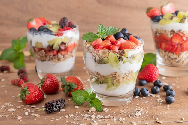 Muesli caseiro, tigela de granola de aveia com iogurte, mirtilos frescos, amora, morangos, kiwi, hortelã e placa de nozes para café da manhã saudável, copie o espaço. conceito de pequeno-almoço saudável. comer limpo.