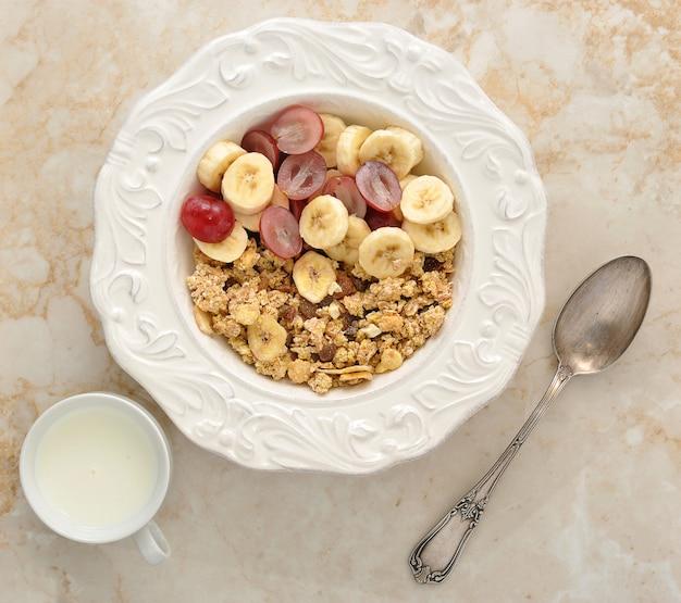 Muesli com banana, uvas e leite. café da manhã saudável.
