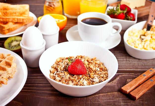 Muesli com frutas frescas, xícara de café, ovos, torradas na mesa