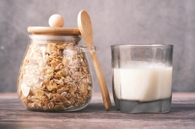Muesli com frutas secas em uma jarra com copo de leite na mesa