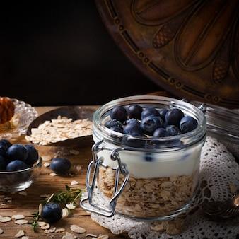 Muesli com iogurte e frutas azuis em frasco de vidro.