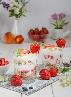 Muesli com iogurte e morangos frescos em um fundo branco de madeira.